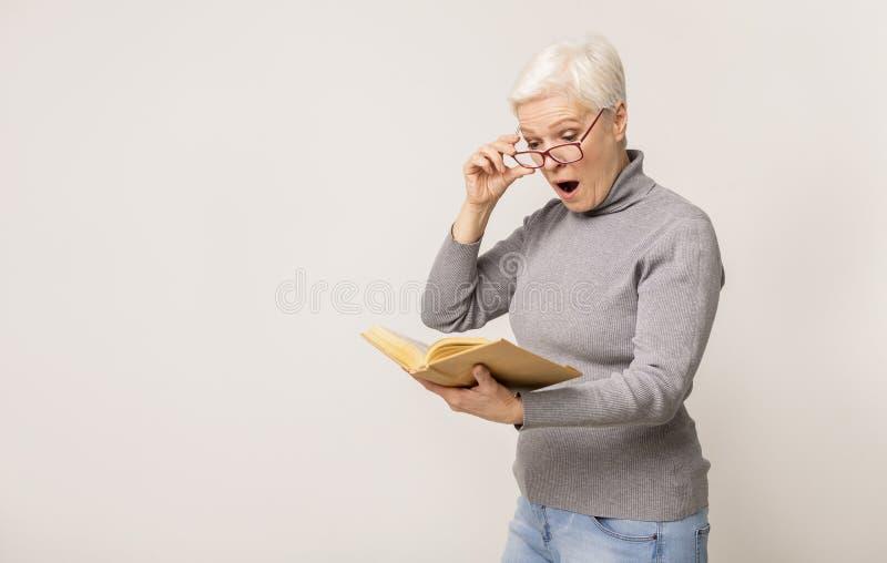 Schokte senere vrouw die boek las en een bril afnam in verbazing stock afbeeldingen