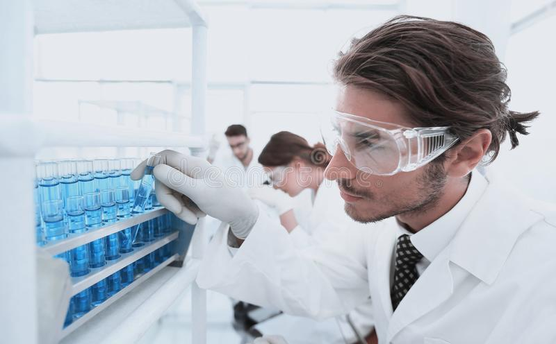 Laboratory assistant in goggles and a lab coat with a test tube. A scholar researcher looks at a blue tube in a laboratory wearing safety glasses and gloves royalty free stock photos