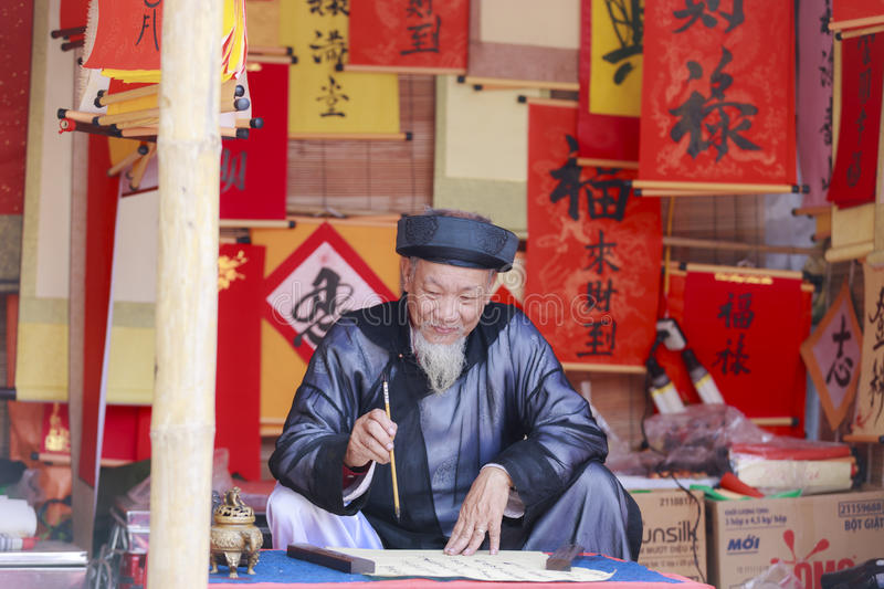 A scholar writes Chinese calligraphy characters at Temple of Literature. HANOI, VIETNAM - JAN, 26: A scholar writes Chinese calligraphy characters at Temple of stock images