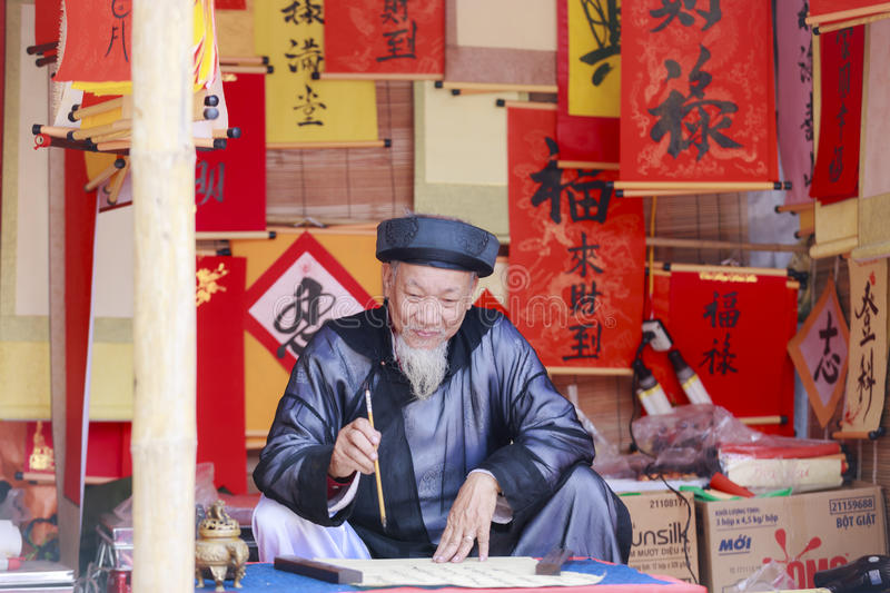 A scholar writes Chinese calligraphy characters at Temple of Literature. HANOI, VIETNAM - JAN, 26: A scholar writes Chinese calligraphy characters at Temple of royalty free stock photography