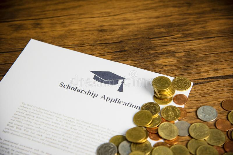 Scholarship application document contract form concept with money coin for grants scholarships education on wooden table stock images