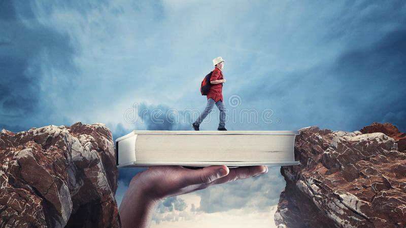 Scholarship concept. The concept of scholarship. Young man passes from a peak to another on a book. The concept of scholarship and stock photography
