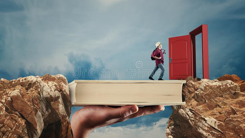 Scholarship concept.  The concept of scholarship and opportunity. Young man passes from a peak to another on a book. Opened door. The concept of scholarship and stock photo