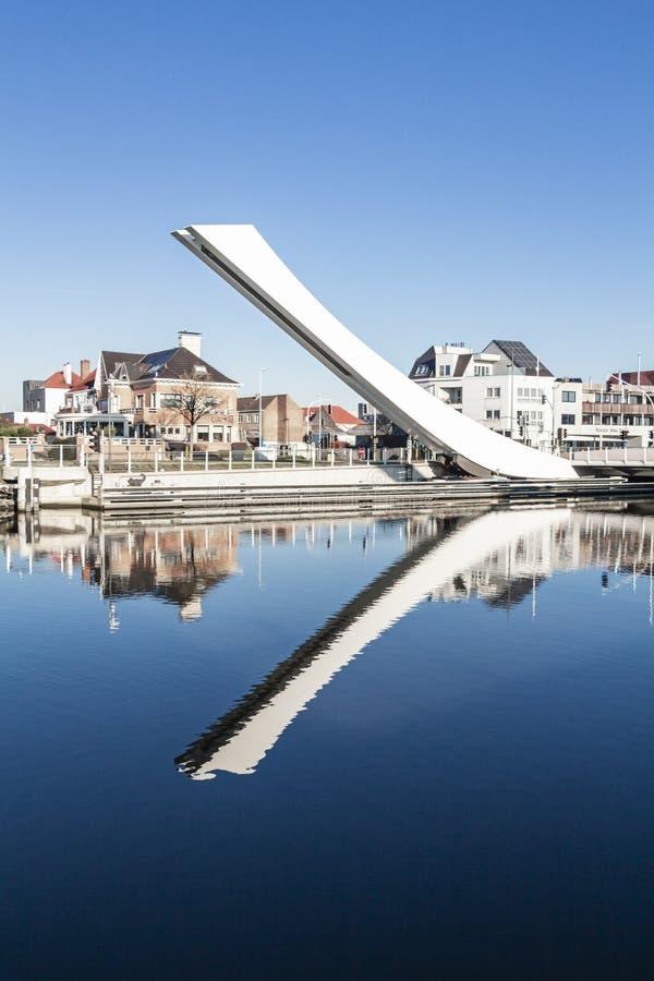Schommelend brugwapen die in water in Brugges - België nadenken stock foto