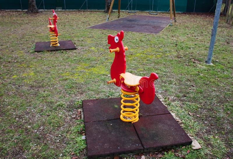 Schommelende spelen voor kleine kinderen rode die schommeling als kleine paarden gestalte wordt gegeven Verlaten speelplaats royalty-vrije stock foto