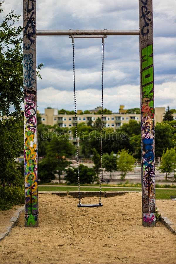 Schommeling in zandbak op speelplaats met graffiti royalty-vrije stock foto