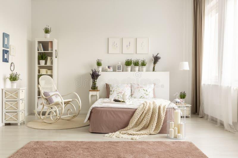 Schommelstoel naast bed met deken in ruim wit slaapkamerbinnenland met roze tapijt Echte foto stock afbeelding