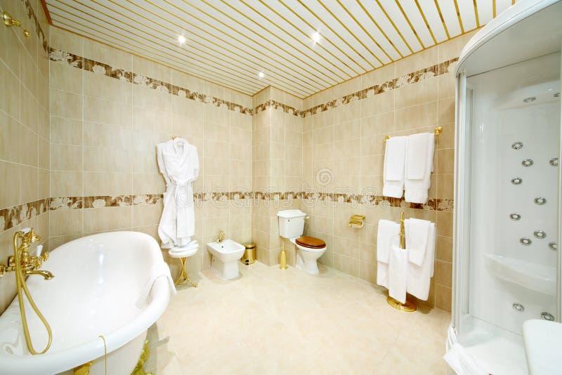 Schone badkamers met bad, douchecabine, toilet en bidet stock foto's