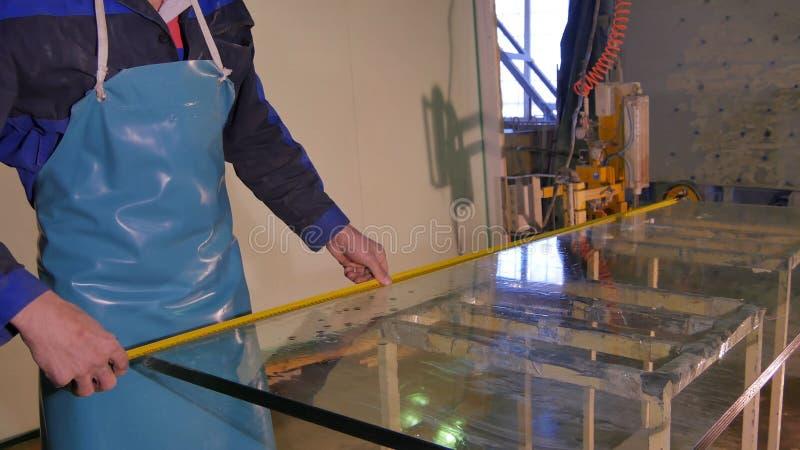 Schone de arbeider en droogt het glas bij de vervaardiging Het glimlachen van medio volwassen arbeiders schoonmakende zeep sud op stock foto's