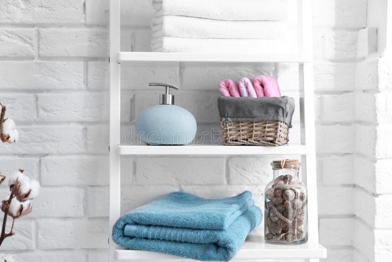 Schone handdoeken met zeepautomaat op planken royalty-vrije stock foto