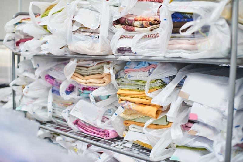 Schone kleren op de planken en Ingepakt in zakken stock afbeelding