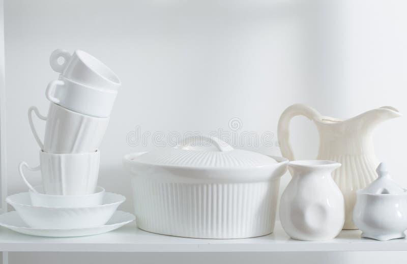 Schone schotels en vazen op witte plank stock afbeelding