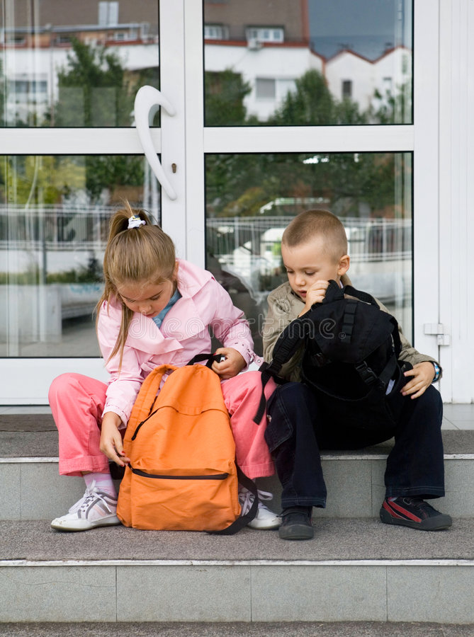 At the school. Primary pupils sitting in front of the school stock photos