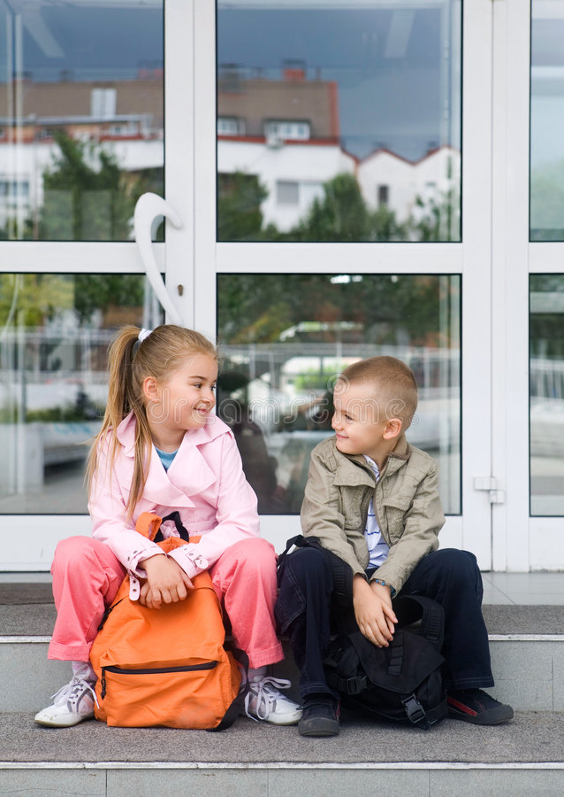 At the school. Primary students in front of the school building on the first day at school royalty free stock image