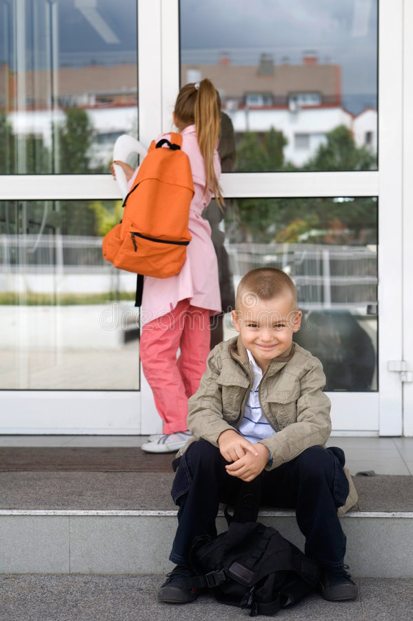 At the school. First day at school, two elemantary students in front of the school building royalty free stock image