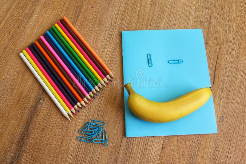Back to school with a smile. School accessoires, colored pencils, paper clips, notebook, banana, smile on wooden background stock photo
