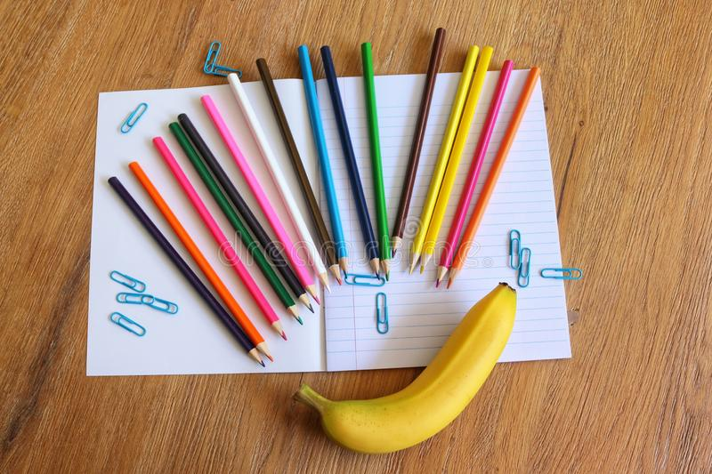 Back to school. School accessoires, colored pencils, paper clips, notebook, banana on wooden background royalty free stock photos