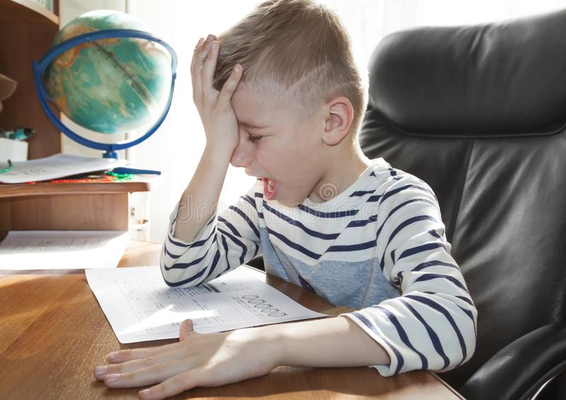 School-age boy crying and screaming while doing homework. the concept of heavy pressure education. Child, student, angry, stress, reading, elementary, young royalty free stock image