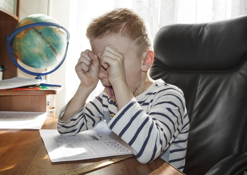 School-age boy crying and screaming while doing homework. the concept of heavy pressure education. Child, student, angry, stress, reading, elementary, young stock images