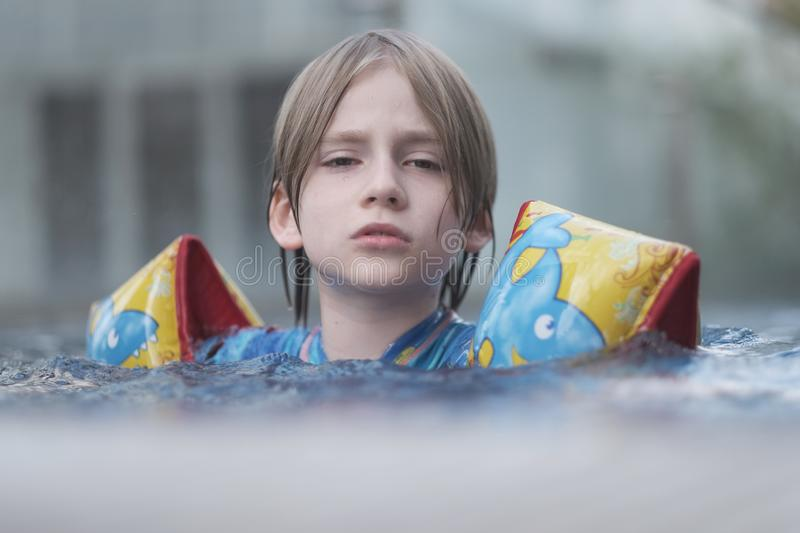 A school-aged child rests on the water surface of the pool stock images