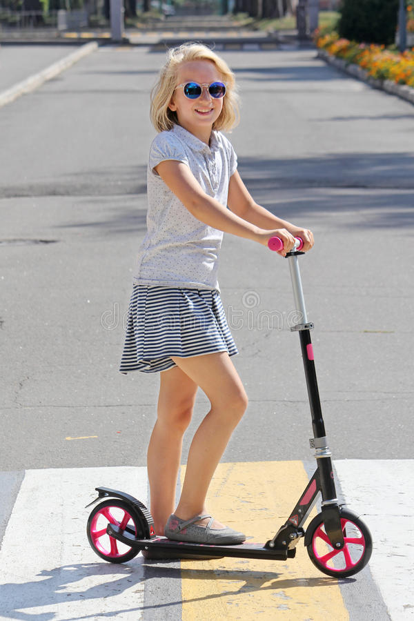 Free School-aged Girl Riding A Scooter. Crosses The Road On A Pedestrian Crossing. Royalty Free Stock Images - 76555939