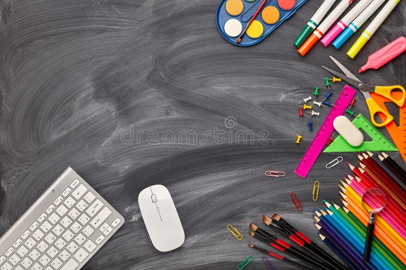 School background. Back to school. Stationery accessories, computer keyboard and mouse on background of school blackboard. Top view, copy space. School stock photography