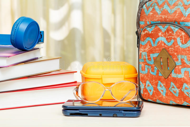 School backpack with school supplies. Books, sandwich box, headphones, glasses and eBook on wooden table royalty free stock photo