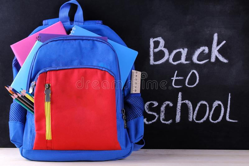 School backpack with school supplies on the background of a school board with the inscription back to school royalty free stock photo