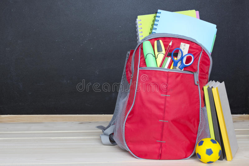 School bag rucksack supplies wooden blackboard background. royalty free stock image