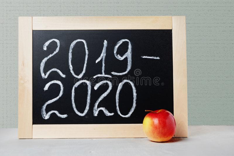School board with text academic year 2019 2020. Background School blackboard and apple.  royalty free stock images