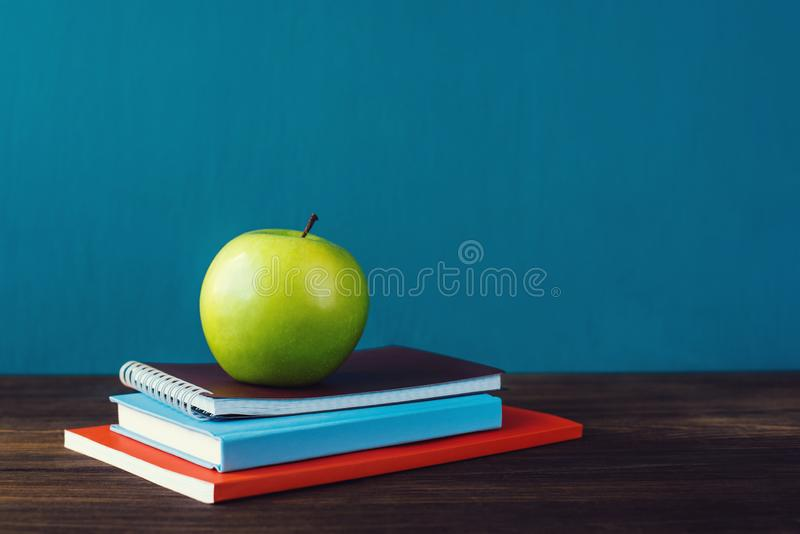 School books with apple on desk royalty free stock images