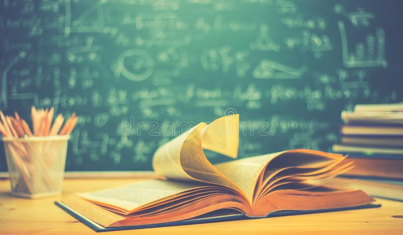 School books on desk formulas and Physics inscription on the blackboard , education concept.  stock photography