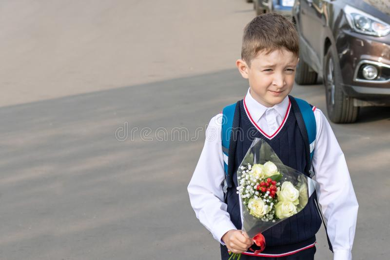 A school boy with a bouquet of white roses in his hand outdoor stock images