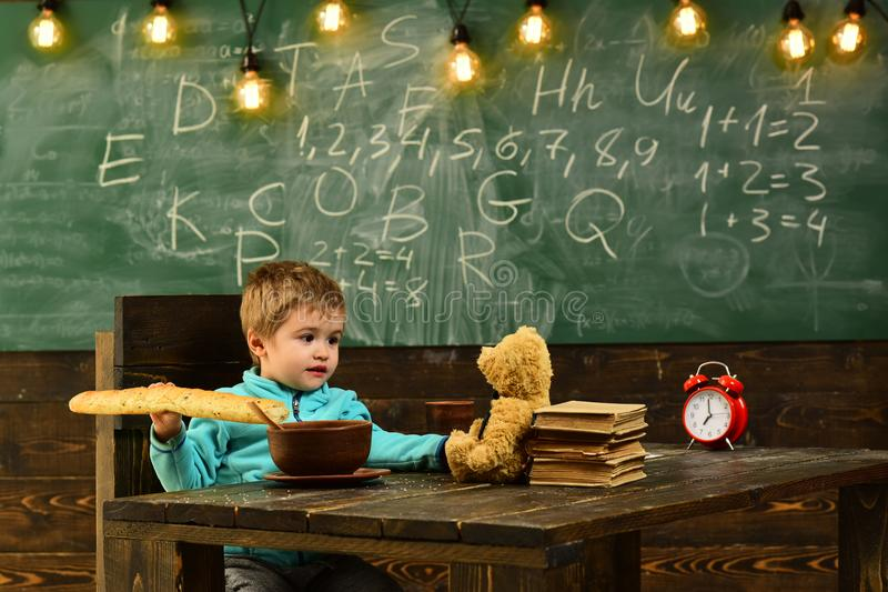 School boy enjoy lunch break with toy friend in classroom. School boy eat food with teddy bear on wooden table. School stock image