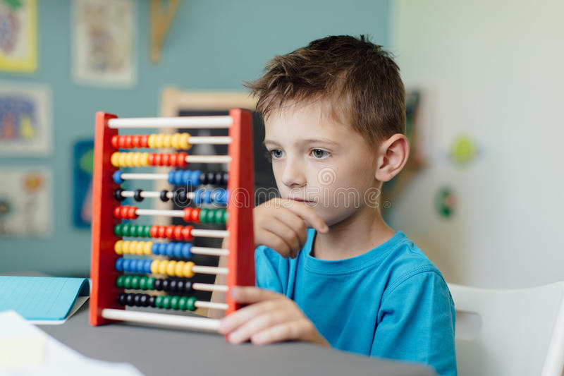 School boy learning maths with an abacus. Portrait of a thinking school boy learning maths with an abacus stock image