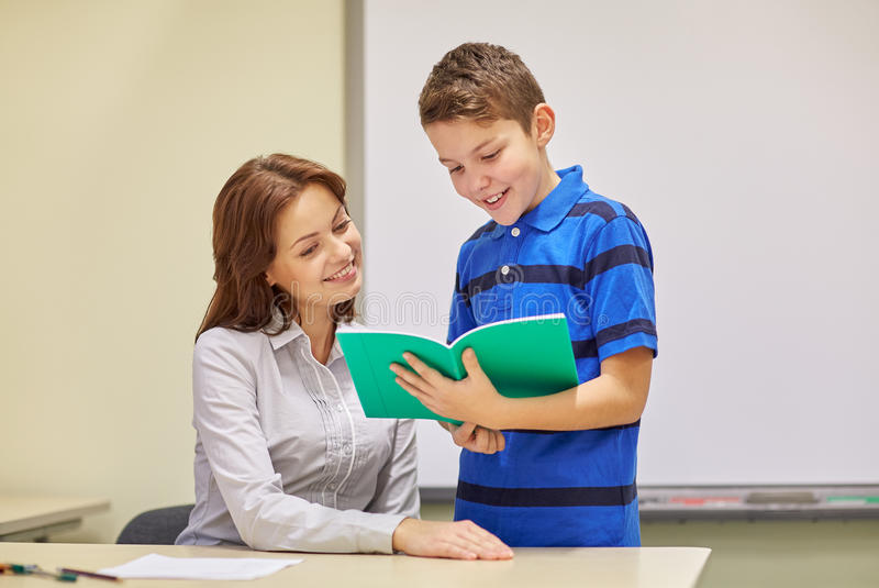 School boy with notebook and teacher in classroom stock photos