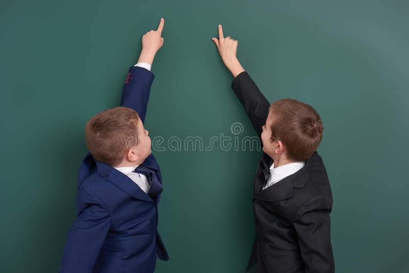 School boy point finger at blank chalkboard background, dressed in classic black suit, group pupil, education concept stock photo