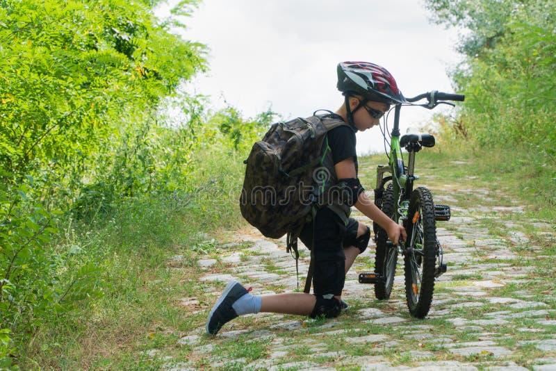 School boy in the protective helmet fix bike in the Park stock photography