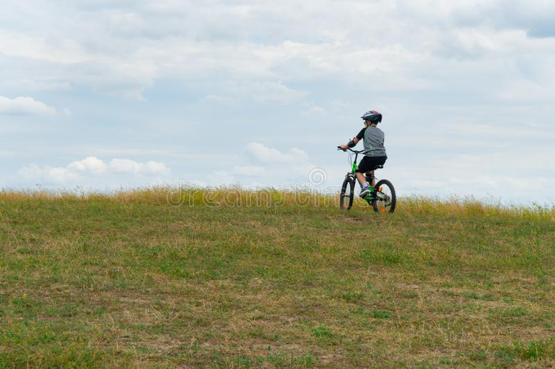 School boy in the protective helmet riding bike in the Park royalty free stock photo