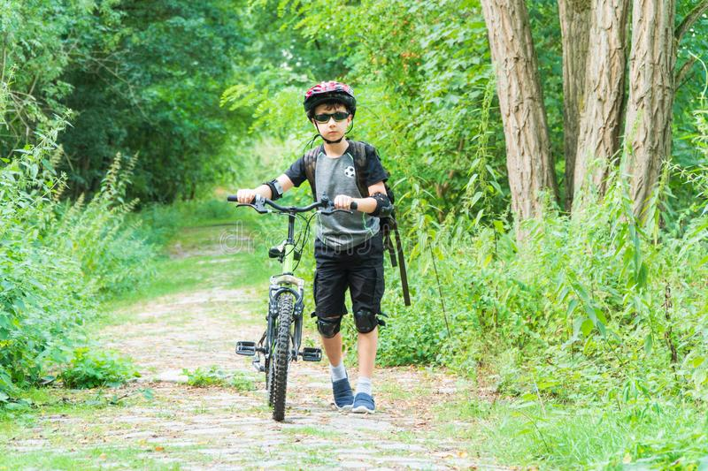 School boy in the protective helmet riding bike in the Park royalty free stock photography