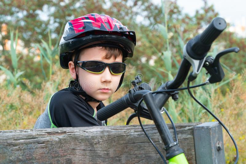 School boy in the protective helmet sits on a bench with bike in the Park stock photo