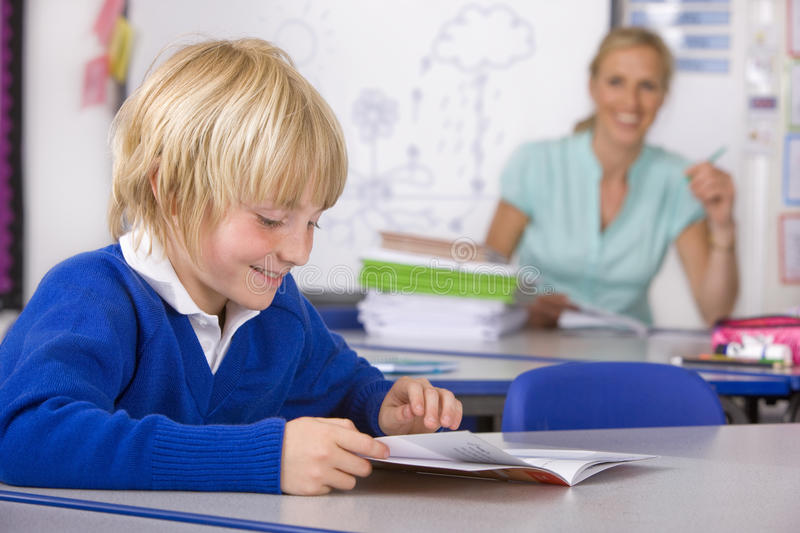 School boy reading workbook in classroom royalty free stock photography