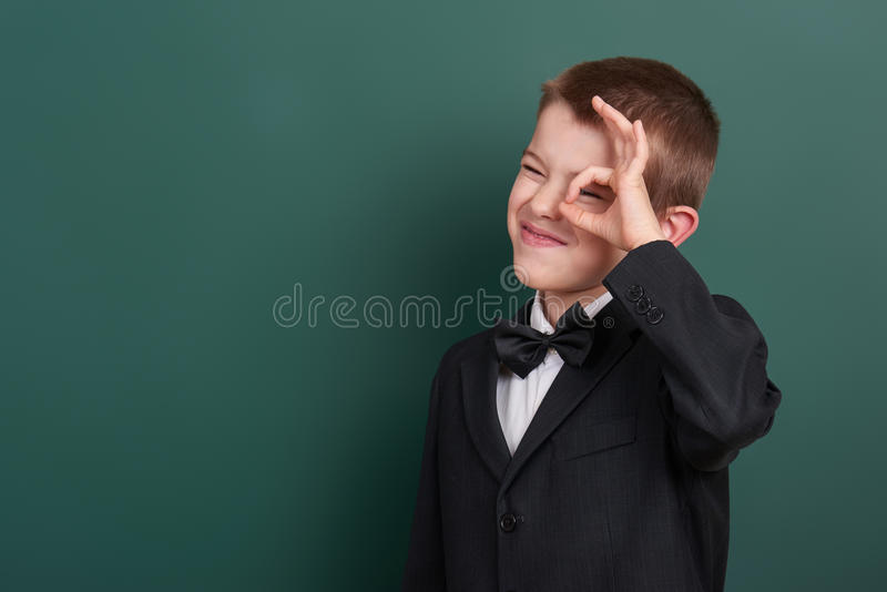 School boy show ok sign, portrait near green blank chalkboard background, dressed in classic black suit, one pupil, education conc. Ept royalty free stock photography