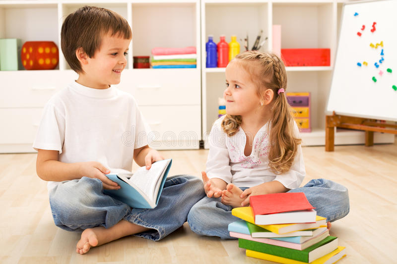 Download School Boy Showing Her Little Sister How To Read Stock Photo - Image: 13111938