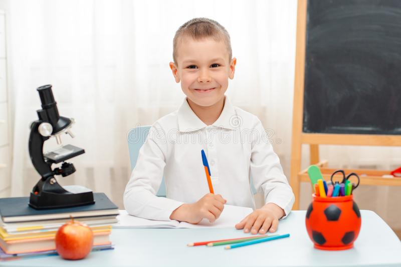 School boy sitting at home classroom lying desk filled with books training material schoolchild sleeping lazy bored royalty free stock image