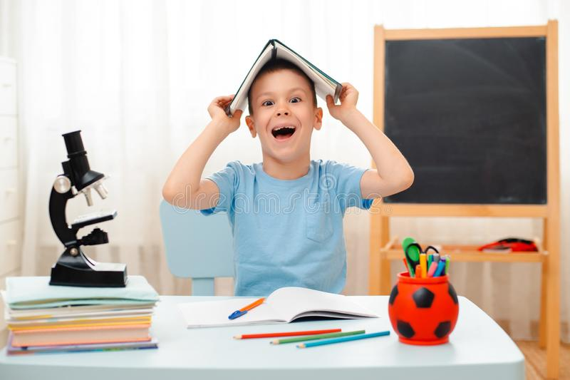 School boy sitting at home classroom lying desk filled with books training material schoolchild sleeping lazy bored royalty free stock images