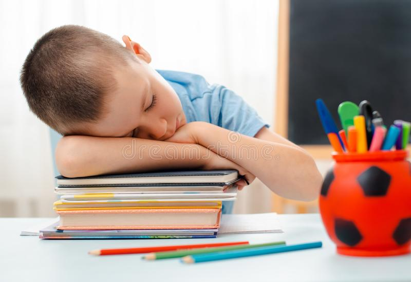 School boy sitting at home classroom lying desk filled with books training material schoolchild sleeping lazy bored stock photography