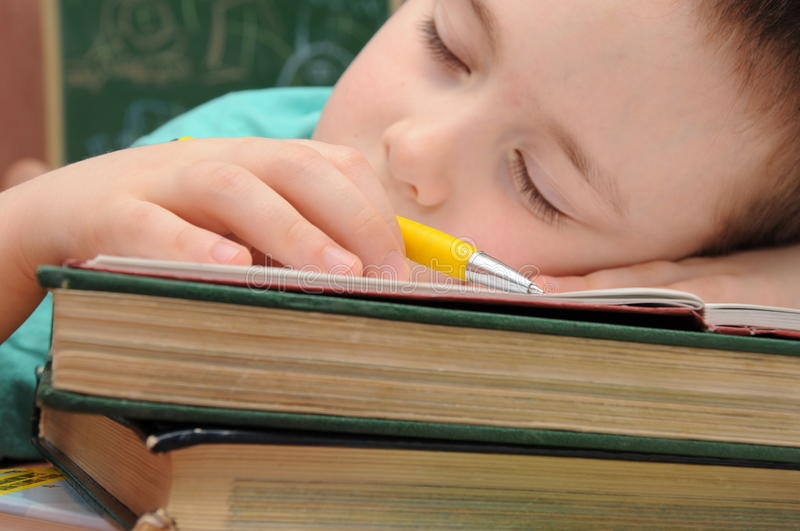 School boy slept on books. School boy dreaming how to write stock photo