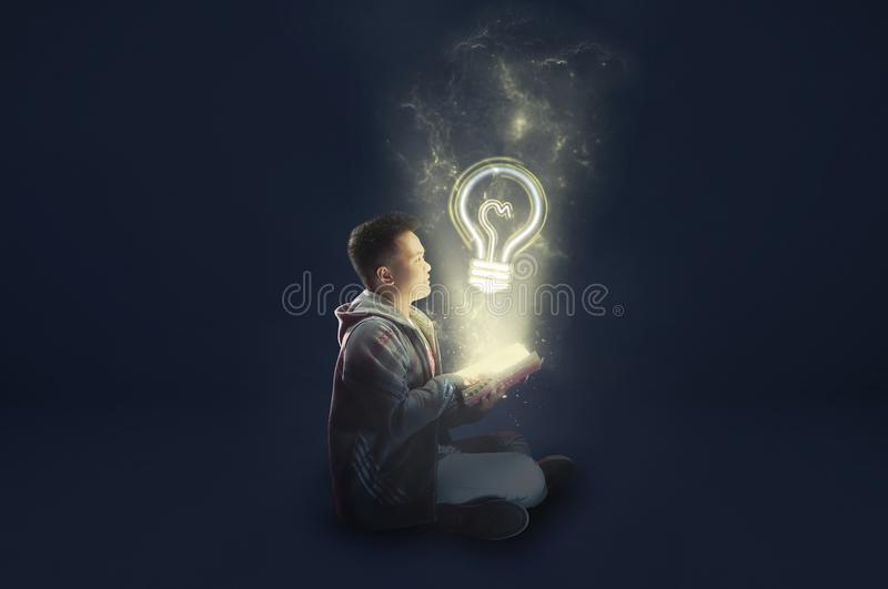 A school boy wearing a jacket holding and reading a magical book with mystical light coming out. Ideas from reading. Depicting edu royalty free stock image