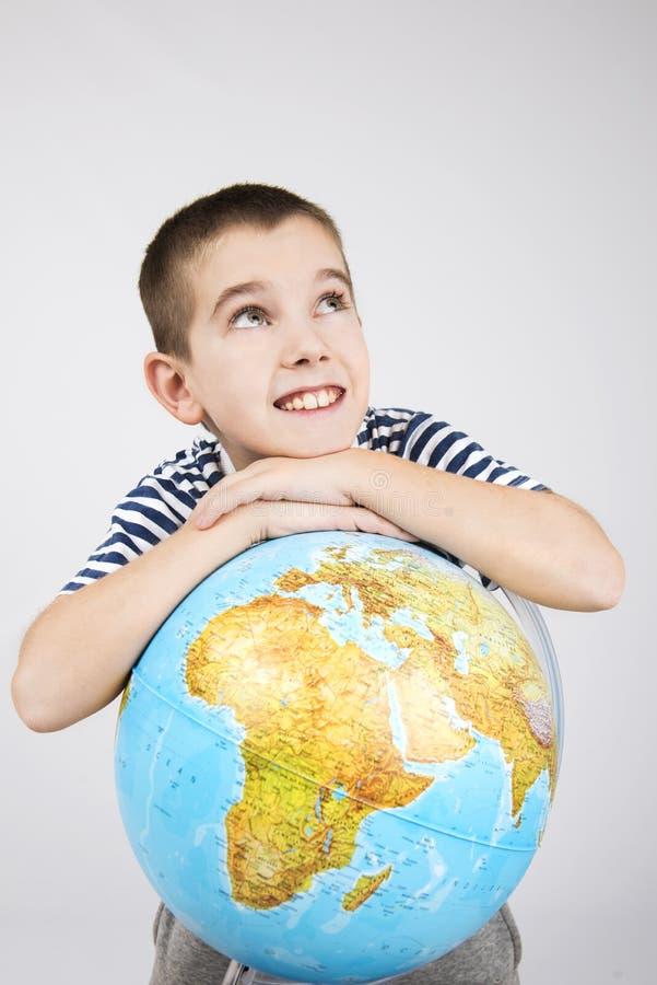 School boy with world globe. Happy school boy thinking about traveling arround World stock image